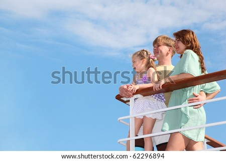 young family rests it at sea and looks far from the deck of yacht - stock photo