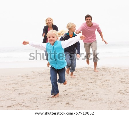 Young Family Running Along Winter Beach - stock photo