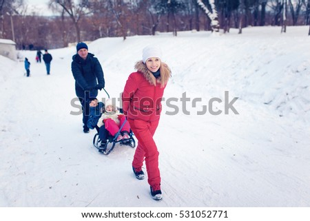 Young Family Running Through Snow With Sled