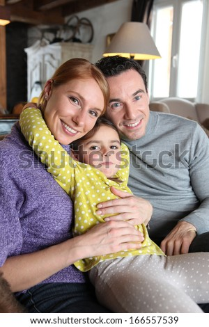 Young family sat on couch - stock photo