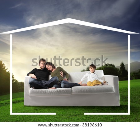 Young family seated on a sofa dreaming a home in the nature - stock photo