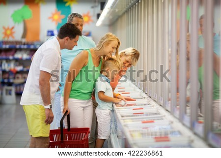 Young family shopping with the Grandparents in a supermarket standing with their young son at a food counter choosing produce - stock photo