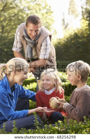 Young family sit together in garden - stock photo