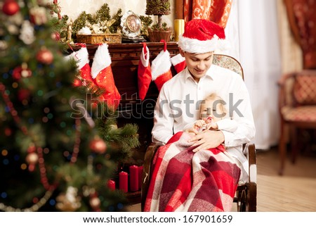 Young family sitting around the Christmas tree. Dad and baby in the New Year  interior.  - stock photo