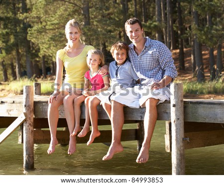 Young family sitting by lake - stock photo