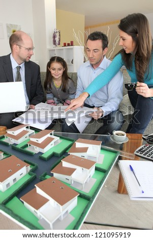 Young family sitting in an architect's office - stock photo