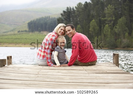 Young family sitting on a jetty - stock photo