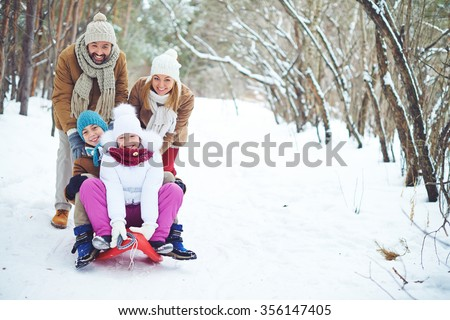 Young family sitting on a sled in the snow