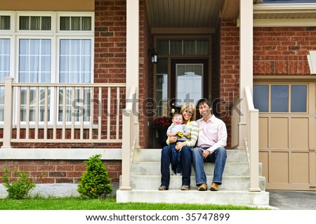 Young family sitting on front steps of house - stock photo