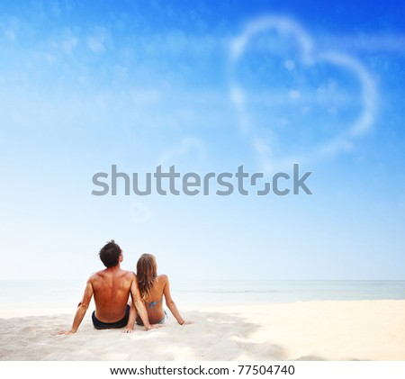 Young family sitting on warm sand by a sea and looking to a blue sky with heart shaped clouds
