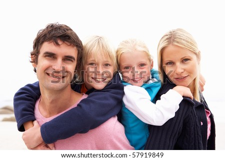Young Family Sitting On Winter Beach - stock photo