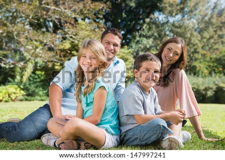 Young family sitting together in park smiling at camera on grass - stock photo