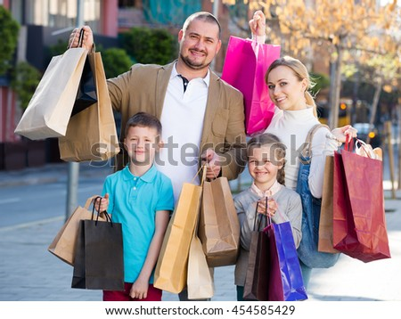 Young family smiling and holding shopping bags in the town
