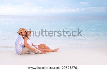 Young family spending summer vacation on romantic beach resort, sitting and hugging on seashore, looking away, affection concept - stock photo
