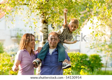 Young family standing in the sun in front homes - single houses - stock photo