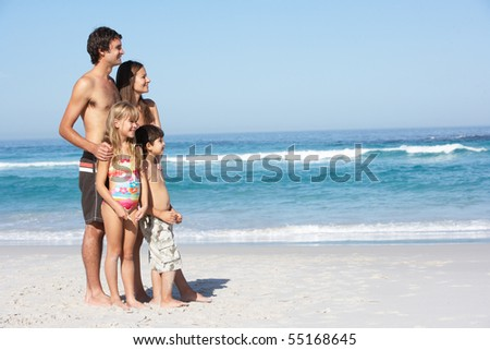 Young Family Standing On Sandy Beach on Holiday