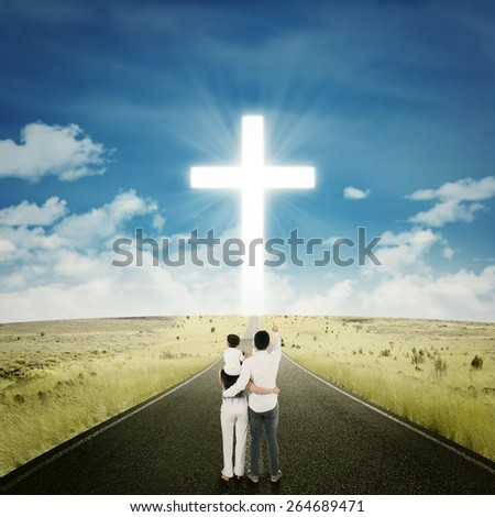 Young family standing on the highway and looking at a cross on the end of the road - stock photo