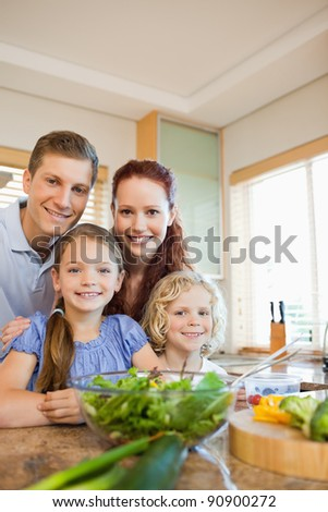 Young family standing together behind the kitchen counter - stock photo