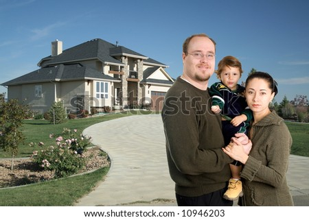Young family standing together in front of luxury home - stock photo