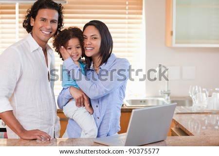 Young family surfing the internet in the kitchen together - stock photo