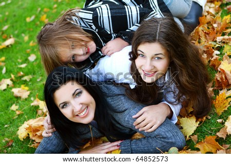 Young family taking healthy stroll through autumn park and have fun - stock photo