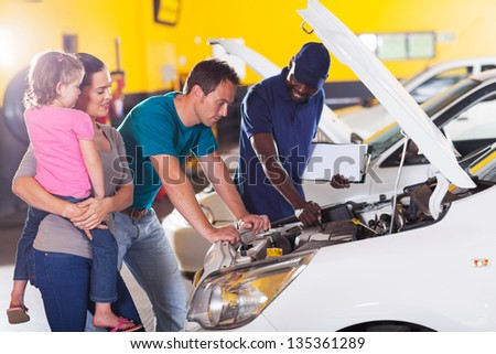 young family taking their car for repair in garage - stock photo