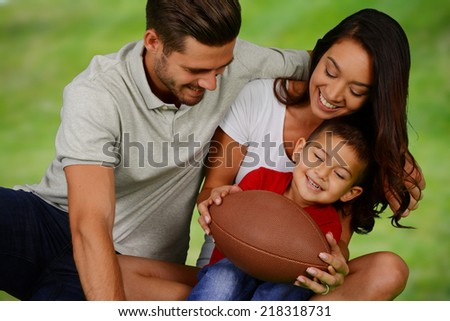 Young family together playing football on a nice day - stock photo