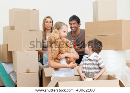 Young family unpacking boxes after move in
