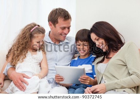 Young family using tablet on the sofa - stock photo