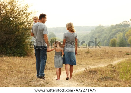 young family walk together on the nature