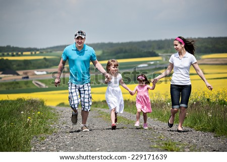 young family walking and ranking the fields