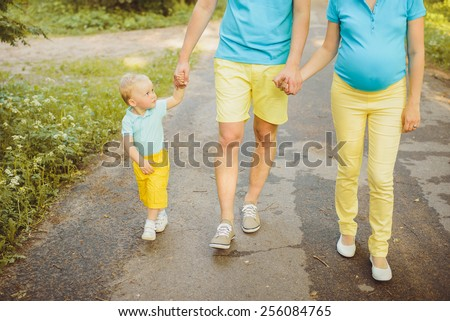 Young family walking holding hands in the park - stock photo