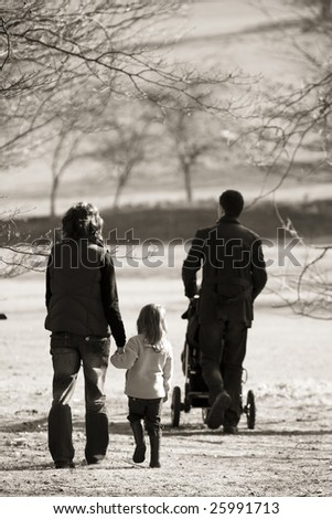 young family walking in open countryside - stock photo