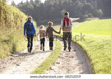 Young family walking in park - stock photo