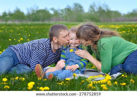 Young family walking on a spring meadow with yellow flowers. - stock photo