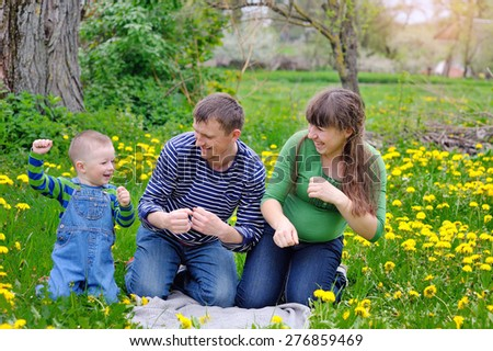 Young family walking on the meadow with yellow flowers in spring. - stock photo