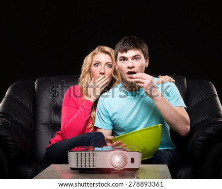Young family watching a movie or a sport broadcast on a laser projector sitting on a sofa  - stock photo