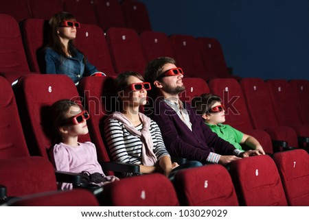 Young family watching a movie with 3D glasses - stock photo