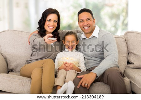 young family watching tv in the living room at home - stock photo