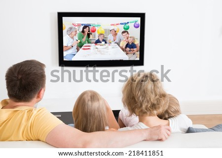 Young Family Watching TV Together At Home - stock photo