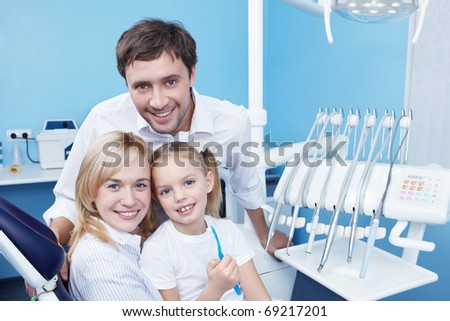 Young family with a child in dentistry - stock photo
