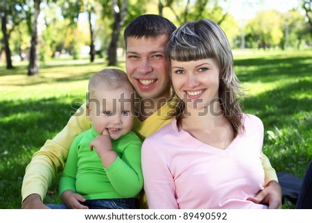 Young family with a child in green summer park