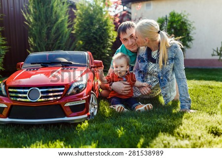 young family with a child playing on the grass outdoor - stock photo