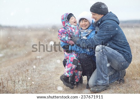 young family with a child playing on winter field