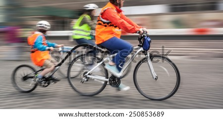 Young family with a child ride a bikes on a city streets. Intentional motion blur and color shift - stock photo