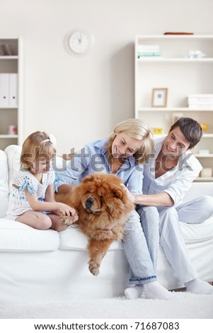 Young family with a dog at home - stock photo