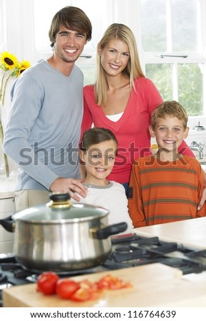 Young family with a small son and daughter posing in the kitchen as they prepare their evening meal - stock photo