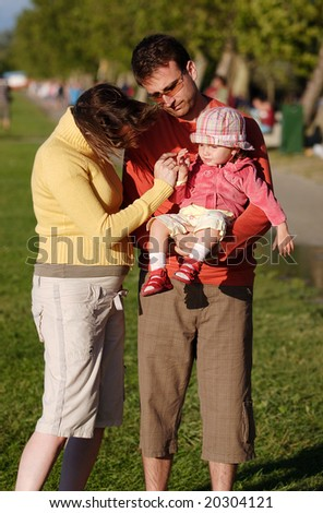 Young family with adorable young child outdoor in autumn