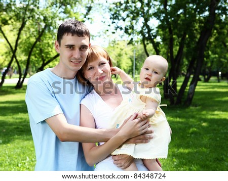 Young family with baby daughter together in the park