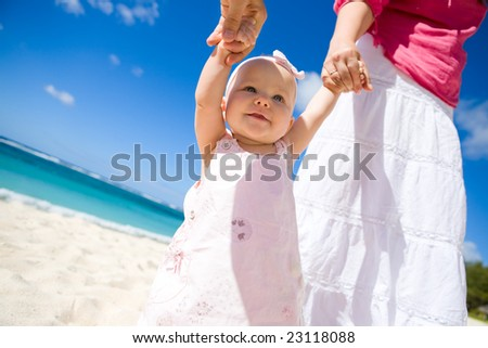 Young family with baby girl on white sand tropical beach - stock photo